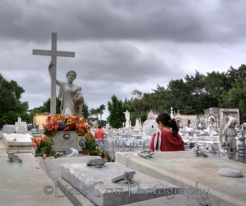 """The most visited place in Necropolis Colon, the grave of Amelia Goyri de la Hoz, a woman known as """"La Milagrosa"""" (""""The Miraculous Woman"""" or """"The Miraculous One""""). An upper-class woman, she died in childbirth in 1901 at age 23, and her stillborn son was placed at her feet when she was buried. According to legend, when the grave was opened years later, her corpse was intact – a sign of holiness – and her son was nestled in her arms. Amelia is considered by many to be Cuba's unofficial saint. Cubans come to her grave every day to ask for children or love affairs.  Colon Cemetery. Havana, Cuba Copyright ©LisetCruz"""
