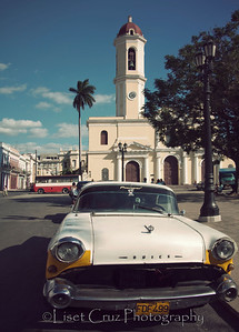 Vintage car with Cathedral.  Parque Jose Marti.  Cienfuegos. Cuba.