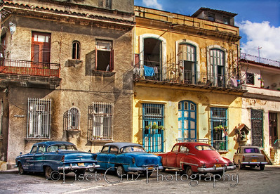 Houses and 4 old cars.  Havana, Cuba.