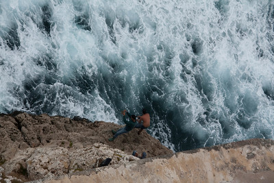 Young men fishing in a dangerous cliff. The Morro Castle. Havana, Cuba.