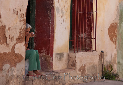 """Drinking a """"buchito de cafe"""" (sip of coffee), a woman seems to be lost in thoughts. Trinidad, Cuba."""