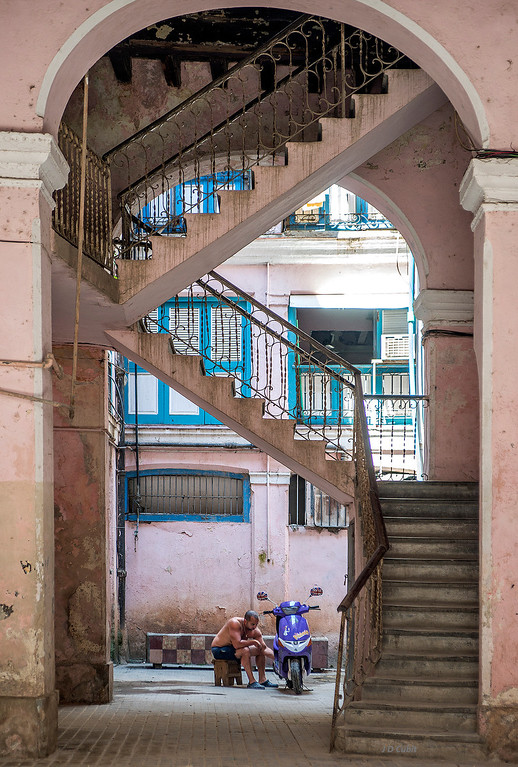 Arched foyer with stairway entering into a patio, Old Havana, where a resident repairs his motorbike.