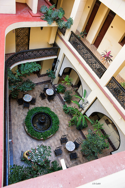 Hotel courtyard.  Much of Cuba's older architecture comes from the Moorish buildings of Andalusia--southern Spain.  Examples of Moorish elements are central sunlit courtyard patios, patio plantings,  arches, extensive tile work, and wrought iron.
