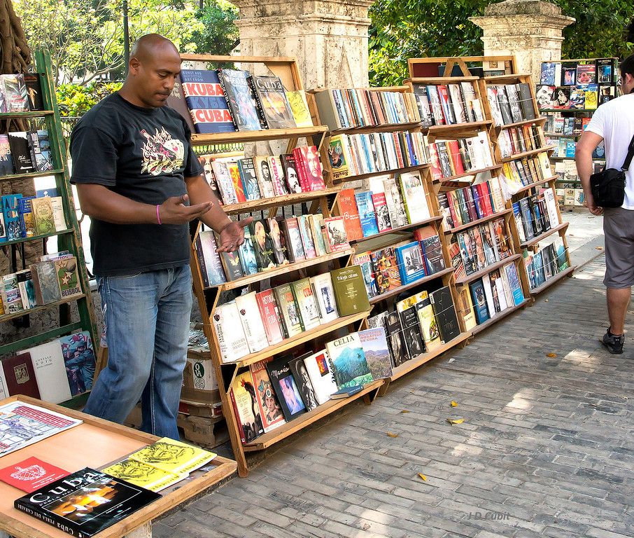 Book seller at his stall in Old Havana's book market plaza.  The paving is wooden blocks.