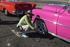 The driver takes care of the pink taxi and polishes the rims.