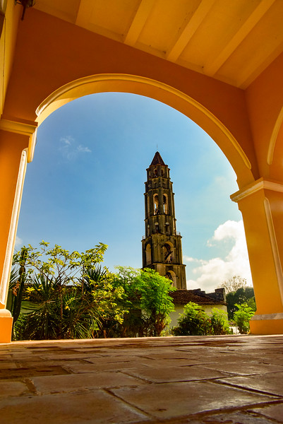 Manaca Iznaga Tower is framed by the arched portico of the beautiful, bold yellow Hacienda Ingenios.