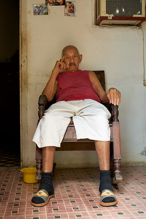 Cuban man sitting in his chair looking out the door, sunny afternoon, Trinidad, Cuba
