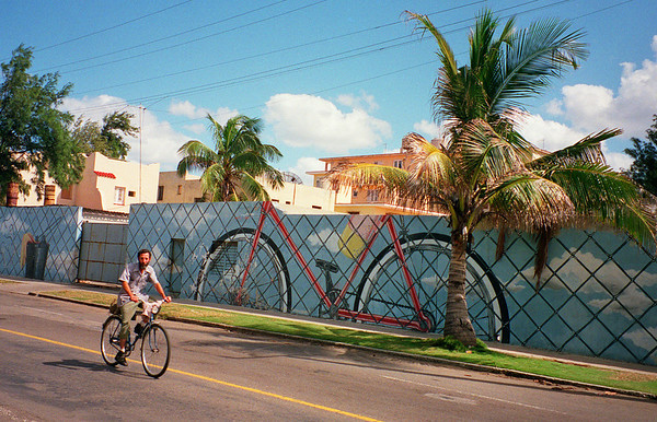 Bicyclist passes national mural promoting usage of newly donated bicycles from China due to the absence of fuel. Miramar, Cuba, February 1993.