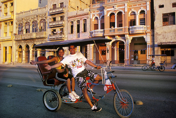 "Cubans on their ""Bici-Taxi,"" for tourists in Old Havana, Cuba, September 2000, after the Cuban government began issuing licenses for small business such as bicycle taxis."