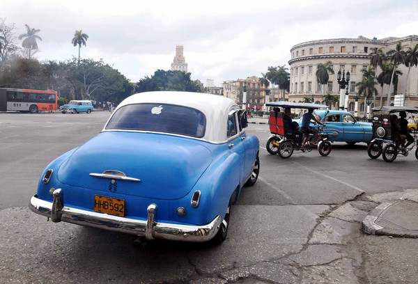 Old American car enjoys new tech times with the Apple logo sticker as the new status symbol in Havana, Cuba, 2013.