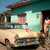 A man fixes his bicycle and old American car in San Antonio de los Baños, Cuba.