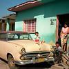 A man fixes his bicycle and old American car in San Antonio de los Baños, Cuba.