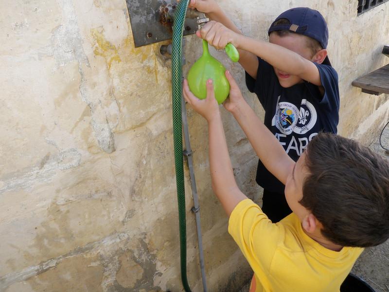 Alan helping Ben fill his water balloon