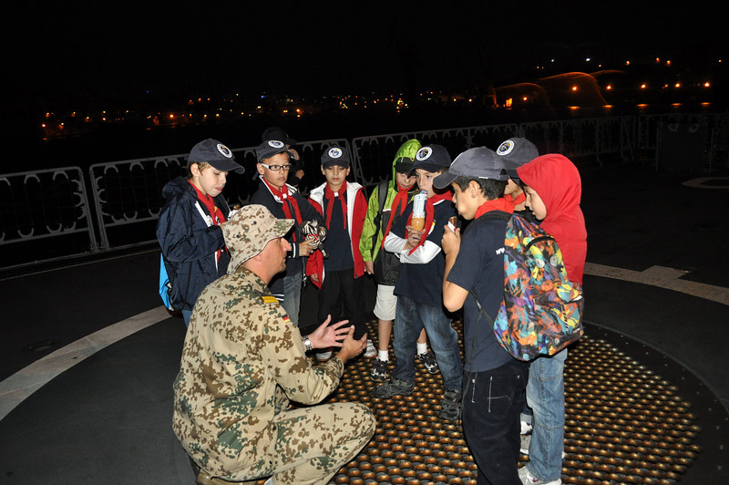 One of the Officers explaining to the Cubs how the helicopter lands and takes off and what the metal grid underneath them is