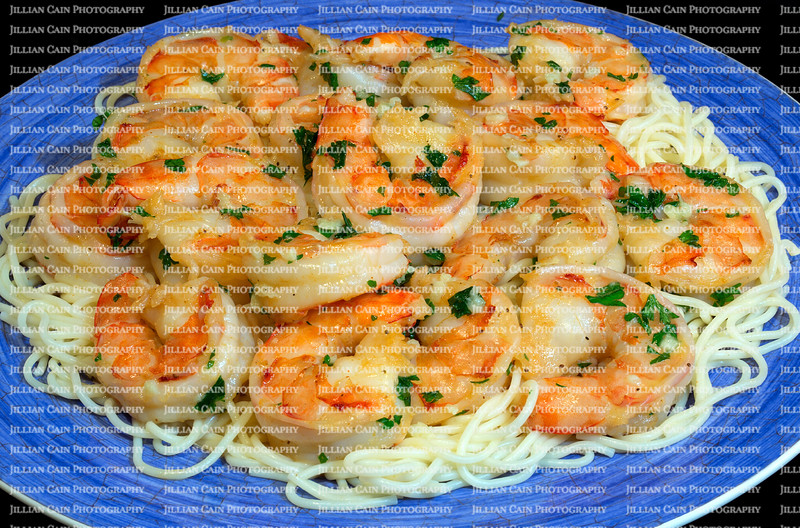 Jumbo shrimp scampi sitting on a bed of pasta