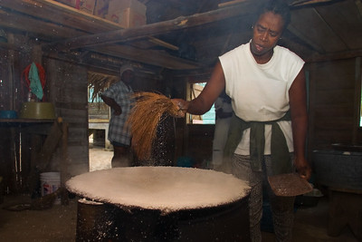 """After the grated, dried and sifted cassava is spread evenly on the """"budari"""" (comal) a """"baisawa"""" (small broom) is used to smoothen the surface and sweep off excess cassava from the top."""