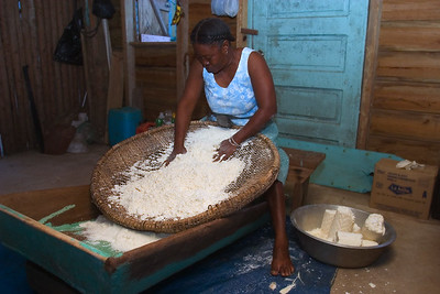 """Sifting (""""ahibiha"""" in garifuna) dry cassava on a """"hibisi"""" (sifter) before it is to be baked."""