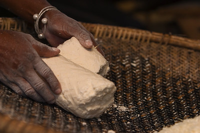 """Breaking apart the dried grated cassava so as to be sifted (""""ahibiha"""" in garifuna) on a hibisi (sifter) before it is baked to make cassava bread."""