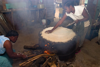 Spreading grated, dried and sifted cassava evenly on a comal over a fire hearth to be baked.