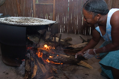 Adding firewodd to the fire hearth to make hot enough before baking cassava bread.