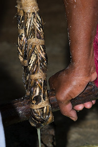 The ruguma (or wowla) full of grated cassava is hung and a stick put through the loop at the bottom so that one can sit on the stick. The weight on the ruguma squeezes the grated cassava and the poisonous juice is drained, leaving the grated cassava dry so it can be sifted and baked to make cassava bread.