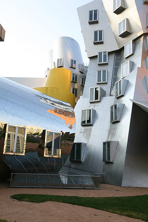 """The Stata Center, MIT  """"the Stata is always going to look unfinished. It also looks as if it's about to collapse. Columns tilt at scary angles. Walls teeter, swerve, and collide in random curves and angles. Materials change wherever you look: brick, mirror-surface steel, brushed aluminum, brightly colored paint, corrugated metal. Everything looks improvised, as if thrown up at the last moment. That's the point. The Stata's appearance is a metaphor for the freedom, daring, and creativity of the research that's supposed to occur inside it.""""  Boston Globe architecture columnist Robert Campbell"""