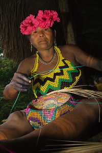 Embera woman weaves a basket out of dyed straws. Chagres National Park, Panama.