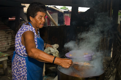 Mestizo woman cooking over fire hearth. She is removing the chicken which is to be used in the preparation of tamales.