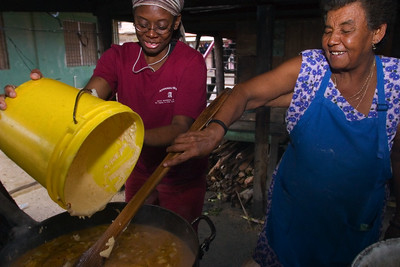 "Mestizo and Garifuna woman adding ingredients into pot over open fire hearth. This part of the process is the boling of the ""col"" which is inside part of the tamales."