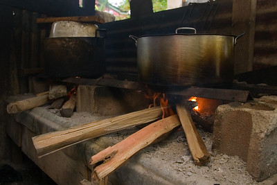 Pot of tamales being boiled on top of fire hearth.