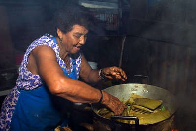 Mestizo woman placing wrapped tamales in pot to be boiled over a fire hearth.