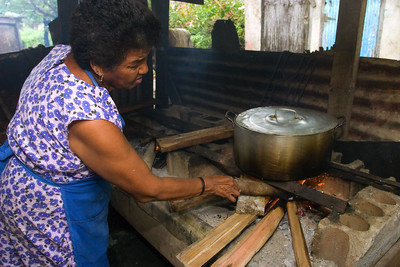 Mestizo woman cooking tamales over fire hearth.