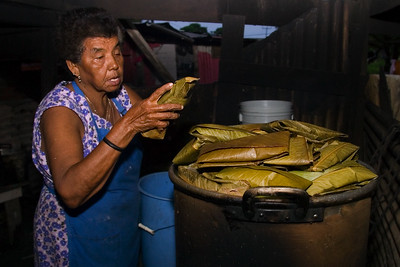Mestizo woman placing wrapped tamales into pot to be boiled over a fire hearth. This is the last process in the making of tamales.
