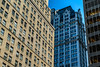 Juxtaposed and overlapping geometric patterns contrast against each other in a street-view of highrise buildings in Manhatten. New York City, NY. USA.