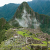 Panoramic view of Machu Picchu ruins   cloaked in early morning mist with Huayna Picchu in the background, Peru