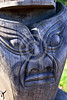 TotPol 00691 A totem pole with a sinister stylistic human face on the bottom, unpainted wood, detail, totem pole picture by Peter J  Mancus