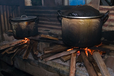 Two pots filled with tamales being boiled over fire hearth.