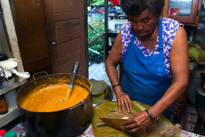 Tamales making - Belizean food preparation in a mestizo kitchen. Placing chicken and col on masa and then wrapping in banana leaf. This will then be boiled.
