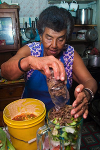 "Tamales making - Belizean food preparation in a mestizo kitchen. Blending ingredients to make ""col""."