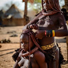 Himba girls working on their traditional hairstyles with clay and ochre braids.  Otjikandero Village, Damara Land, Namibia.  Africa.