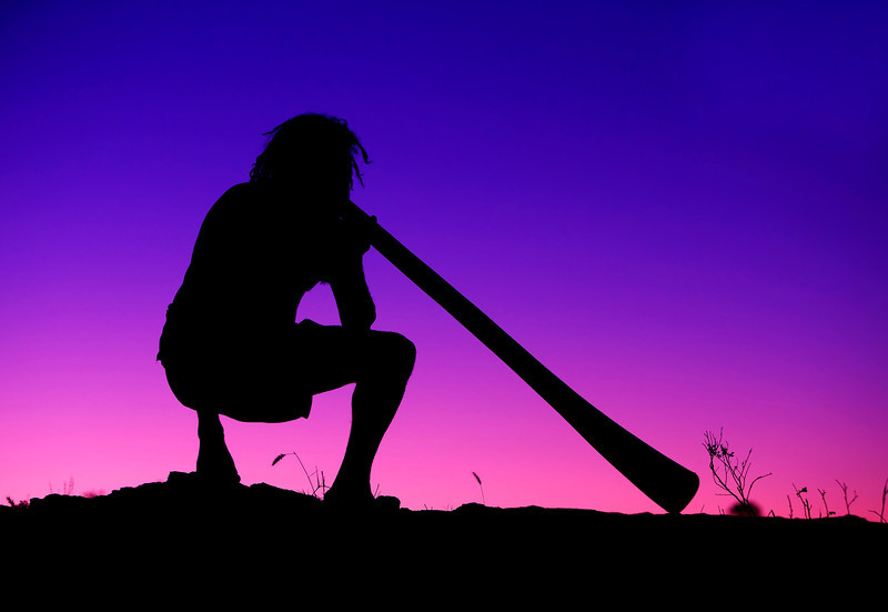 Aboriginal playing Didgeridoo at sunset.  Alice Springs. Australia.