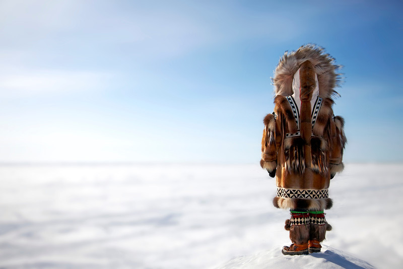 Inupiaq Eskimo woman overlooks the frozen Bering Sea.  Nome, Alaska