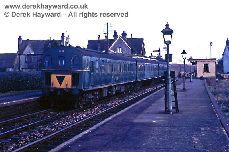 """Barcombe Mills station, looking north, on Sunday 23.02.1969.  1318 is about to depart (towards the camera) on the 11:00 """"wrong line"""" shuttle service to Lewes.  For some reason the paintwork on the first class section of the train appears to have failed.  The photo catches the signalman opening the level crossing to road traffic. To the right the picture also shows a small section of the disused bay platform that was used for goods traffic only.  A step ladder for lighting the lamps leans against one of the lamps, to which is affixed a """"3-car stop"""" marker (facing away from the camera).  Eric Kemp retains all rights to this image."""