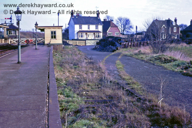 The former goods yard at Barcombe Mills station, looking north, on 23.02.1969.  There are still sleepers in the old goods bay, and the curving lines of grass mark the former long siding leading to the large mill in the village.  The mill was almost completely destroyed by fire in 1939 and the remains were subsequently demolished.  The coal merchant was still in business, and given the position of the bins it seems likely that (before closure) the mill siding was also used to offload coal from rail wagons direct into the bunkers.  Eric Kemp retains all rights to this image.