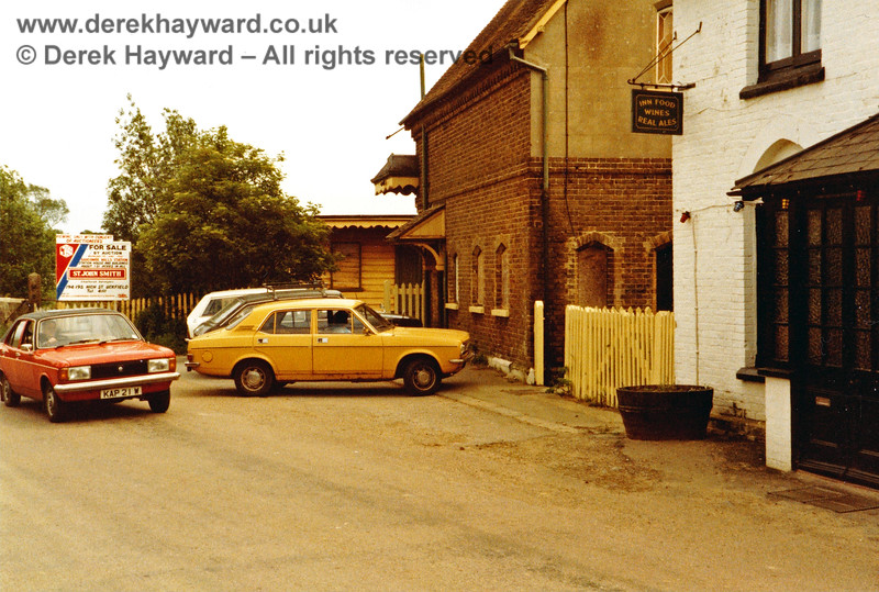 """Outside Barcombe Mills station, looking east in 1983, prior to auction. The necessary """"For Sale by Auction"""" notice is very prominent. On the right the picture just catches the """"Angler's Rest"""" public house (formerly the """"Station Inn"""").  Clearly the name had been changed to exploit the most likely source of trade, but the pub closed in the 1990s.  Nick Mander retains all rights to this image."""