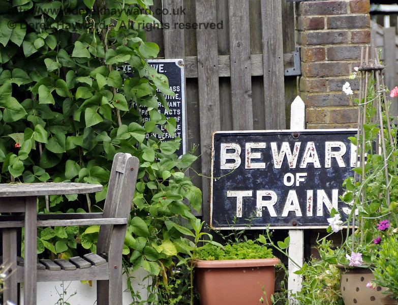 The garden of the former Barcombe Mills station, with some railway signs lurking in the undergrowth. 28.07.2014 11379.  Please note that this location is private property (I was there on Bluebell Railway business).