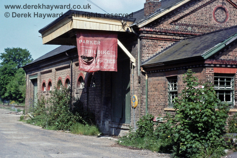 """The former goods shed at Uckfield, in somewhat overgrown condition on 25.05.1991.  The """"Parker Building Supplies"""" sign had also seen better days.  Two large doors for loading road vehicles are in shot; the shed was of an appropriate size to serve the growing town.  Eric Kemp retains all rights to this image."""