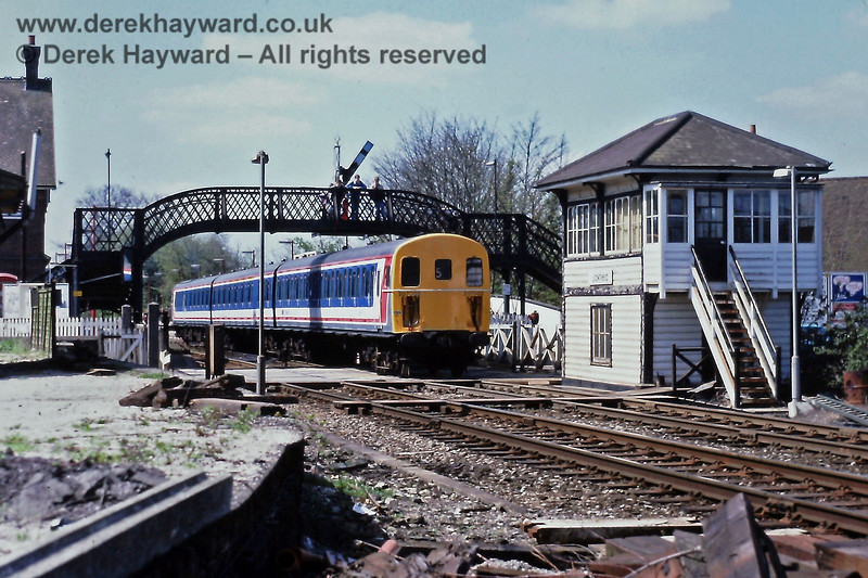 207002, freshly painted in Network South East livery, departs north from Uckfield on Saturday 23.04.1988.  The unit's number appears above both sets of jumpers and not in the usual position.  Happily that idea did not last long.  The photographer is standing in the former rail access to a short goods dock by the mill, the curved wall showing the route of the track towards the camera.  Eric Kemp retains all rights to this image.