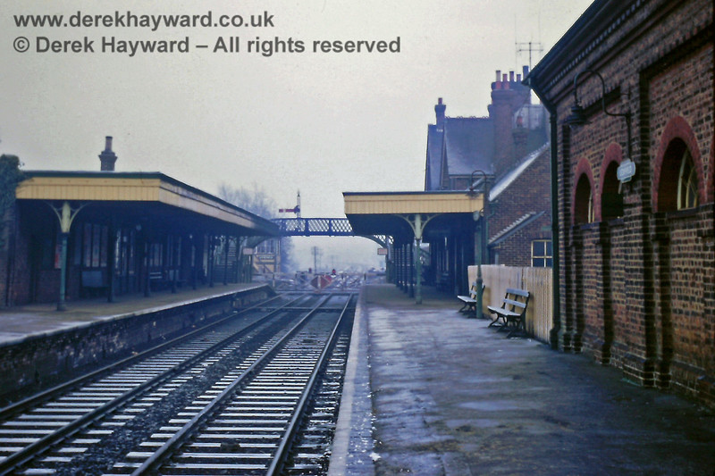 Uckfield Station, looking north on 01.01.1969.  A recent fall of snow had largely melted but it remained damp and murky.  The wall of the goods shed is on the right, and the signal box can just be seen beyond the level crossing.  The goods yard is behind the camera and was entered from the south.  Eric Kemp retains all rights to this image.