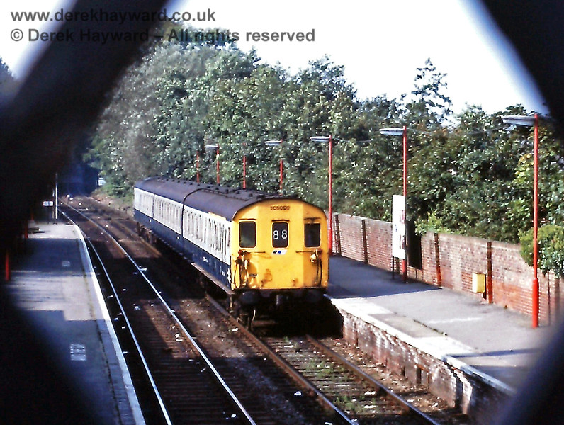 Framed by the diamond shapes of the footbridge, 205002 shunts into the Up platform to form the 11:42 departure from Uckfield on Saturday 03.10.1987.  The unit would be better known as 1102, and carries one of many livery variations seen on this line.  In this case blue and grey with a Network South East badge below the route indicator.  The lamp posts are also in NSE red.  Once painted red many of the posts on the line remained in that colour for many years as the stations deteriorated and suffered a disappointing lack of maintenance.  Eric Kemp retains all rights to this image.